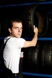Mecánico joven que alcanza el neumático en servicio del coche Imagen de archivo