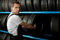 Mecánico joven que sostiene un neumático de coche Imagen de archivo libre de regalías