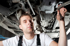 Mecánico joven que trabaja debajo del coche en garage Imagenes de archivo