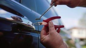 Mecánico o ladrón de sexo masculino que lleva a cabo el lockpicker para abrir la puerta de coche Cierre para arriba metrajes