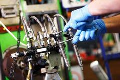 Mecánico profesional que prueba el inyector diesel en su taller foto de archivo libre de regalías