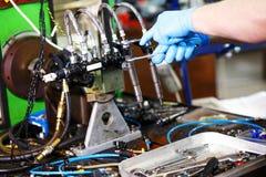 Mecánico profesional que prueba el inyector diesel en su taller imágenes de archivo libres de regalías