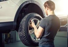 Mecánico que ajusta la rueda del neumático en el garaje de la reparación Fotografía de archivo