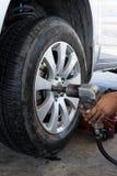 Mecánico que atornilla o que desatornilla la rueda de coche cambiante Imagen de archivo