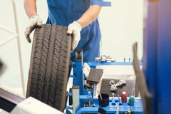 Mecánico que cambia una rueda de un coche moderno en un taller Foto de archivo