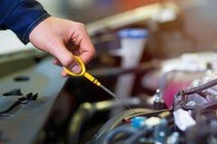 Mecánico que comprueba el aceite de motor en taller de reparaciones auto imagenes de archivo