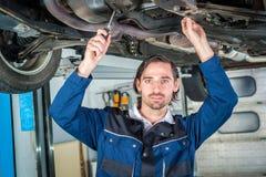 Mecánico que comprueba la condición de un coche levantado Imágenes de archivo libres de regalías