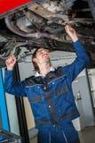 Mecánico que comprueba la condición de un coche levantado Imagen de archivo