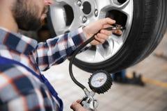 Mecánico que comprueba presión de neumáticos en centro de servicio imágenes de archivo libres de regalías