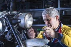 Mecánico que desatornilla la linterna de la motocicleta Foto de archivo