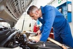 Mecánico que examina debajo de la capilla del coche con la antorcha imagenes de archivo