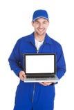 Mecánico que exhibe el ordenador portátil sobre el fondo blanco Fotos de archivo libres de regalías