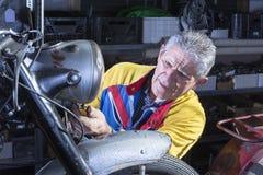 Mecánico que fija la linterna de la motocicleta Fotografía de archivo libre de regalías