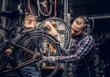 Mecánico que hace el manual.N-POS=30 de reparaciones de la rueda de bicicleta en un taller Foto de archivo libre de regalías