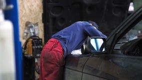 Mecánico que hace un diagnóstico debajo de la capilla del coche en la tienda del servicio metrajes