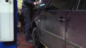 Mecánico que hace un diagnóstico debajo de la capilla del coche en la tienda del servicio almacen de video