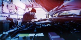 Mecánico que mira el motor de coche foto de archivo