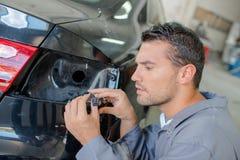 Mecánico que mira los cables para el indicador del coche Imagenes de archivo
