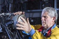 Mecánico que monta la linterna de la motocicleta Imagen de archivo libre de regalías