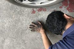 Mecánico que pone detrás del coche y que mira debajo del coche fotos de archivo