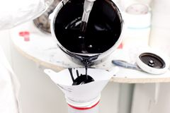 Mecánico que prepara la pintura negra para trabajar en un coche en g especial Fotografía de archivo