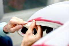 Mecánico que prepara un coche para pintar protegiendo los bordes Imágenes de archivo libres de regalías