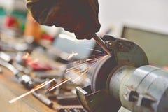 Mecánico que pule un tornillo en la máquina pulidora industrial Imagen de archivo