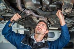 Mecánico que repara un ingenio levantado del coche Imágenes de archivo libres de regalías