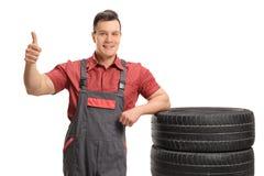 Mecánico que se inclina en los neumáticos y que hace el pulgar encima de la muestra Imagen de archivo
