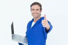 Mecánico que sostiene el ordenador portátil mientras que muestra los pulgares para arriba Fotos de archivo