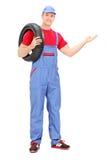 Mecánico que sostiene un neumático y que gesticula con la mano Imagenes de archivo