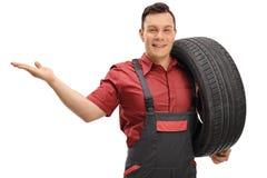 Mecánico que sostiene un neumático y que gesticula con su mano imágenes de archivo libres de regalías