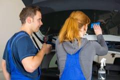 Mecánico que teñe la ventanilla del coche con la hoja o la película teñida Imagen de archivo