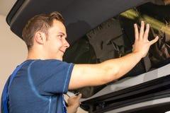 Mecánico que teñe la ventanilla del coche con la hoja o la película teñida Fotos de archivo