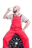 Mecánico que toma una rotura y que bebe el café Imagenes de archivo