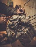 Mecánico que trabaja con con el motor de la motocicleta Imagenes de archivo