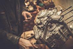 Mecánico que trabaja con con el motor de la motocicleta Fotos de archivo libres de regalías
