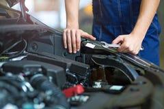 Mecánico que trabaja en el motor de coche en taller de reparaciones auto foto de archivo libre de regalías