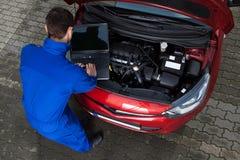 Mecánico que usa el ordenador portátil mientras que repara el coche imagenes de archivo