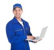 Mecánico que usa el ordenador portátil sobre el fondo blanco foto de archivo libre de regalías