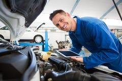 Mecánico que usa la tableta en el coche Imagenes de archivo