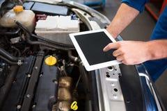 Mecánico que usa la tableta para fijar el coche Fotos de archivo libres de regalías