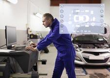Mecánico que usa PC de sobremesa en el garaje imagen de archivo