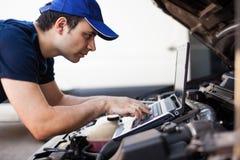 Mecánico que usa un ordenador portátil para comprobar un motor de coche foto de archivo