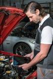Mecánico que usa una PC de la tableta en el garaje de la reparación Imagen de archivo