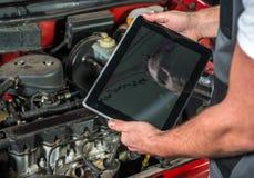 Mecánico que usa una PC de la tableta en el garaje de la reparación Imágenes de archivo libres de regalías