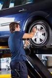 Mecánico Refilling Car Tire en el garaje fotografía de archivo libre de regalías