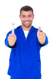 Mecánico sonriente que detiene a la llave inglesa mientras que gesticula los pulgares para arriba Imagen de archivo