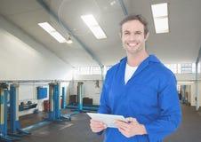 Mecánico sonriente que sostiene la tableta digital en garaje imagen de archivo libre de regalías