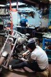 Mecánico tatuado Repairing Chopper Bike Fotografía de archivo libre de regalías